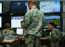 Four soldiers utilizing DRRS training programs assessing critical Real-time information for the planning and execution of assigned missions that affect the security of our nation and how we assist other nations in crisis.
