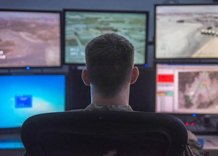 Image of soldier monitoring real time data.